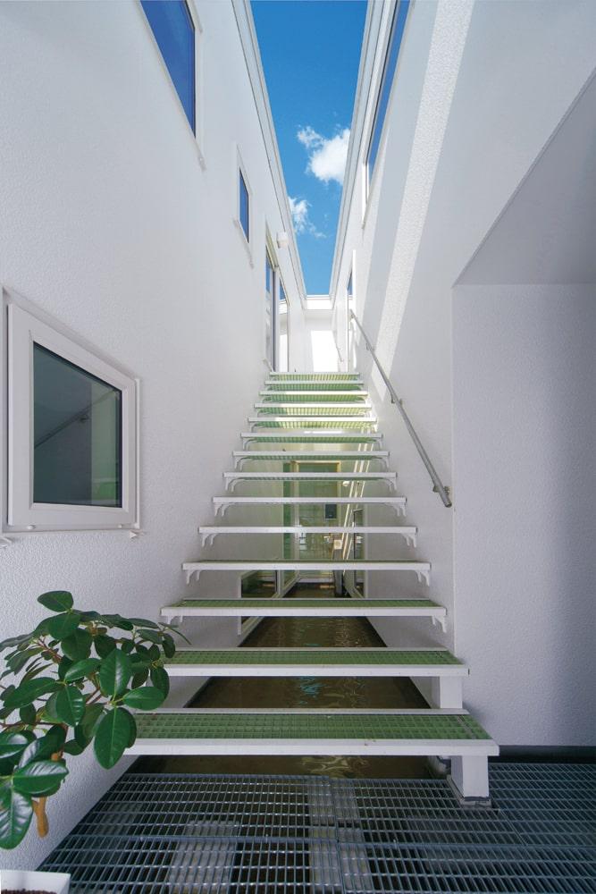 玄関脇に設けた「ギャラリー」と呼ばれる中庭空間は、2階の屋上庭園へつながる。東西に長いギャラリーは、光の入りにくい室内を明るくする、もうひとつの南の壁面にもなっている