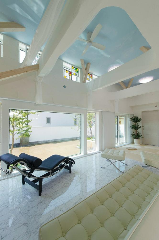ダイナミックな吹き抜けが頭上に広がる開放的なリビング。高窓から射し込む外光と、水盤からの反射光がリビング背面にあるダイニング・キッチン空間も明るく照らす