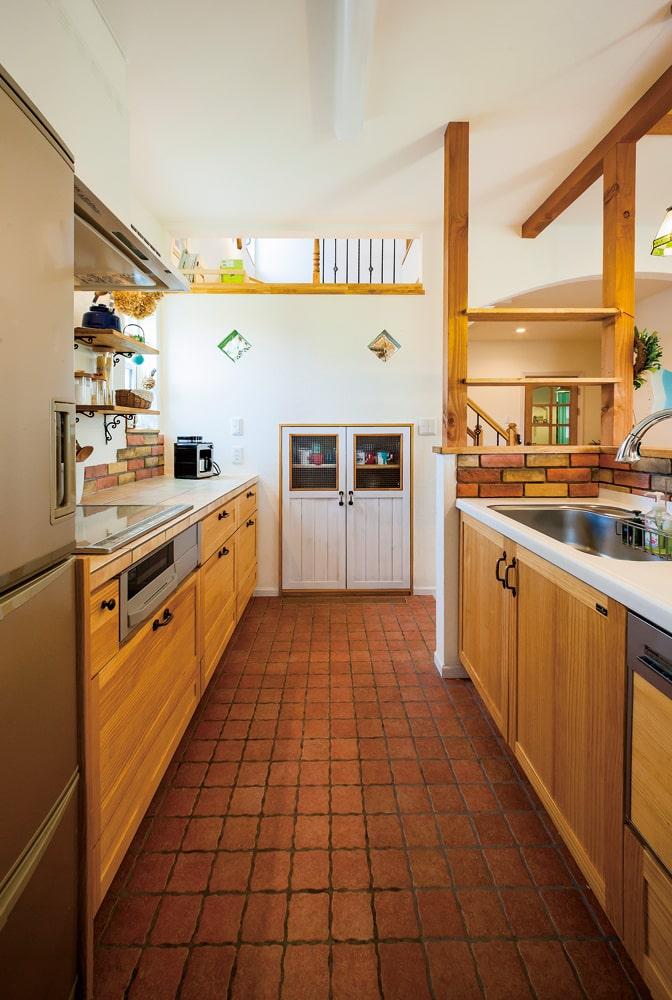 奥さんのセンスが発揮されたキッチン。シンクとIHクッキングヒーターをあえて離すことで、手狭な感じを解消した。ウッドワンのムク材の扉が雰囲気にマッチ