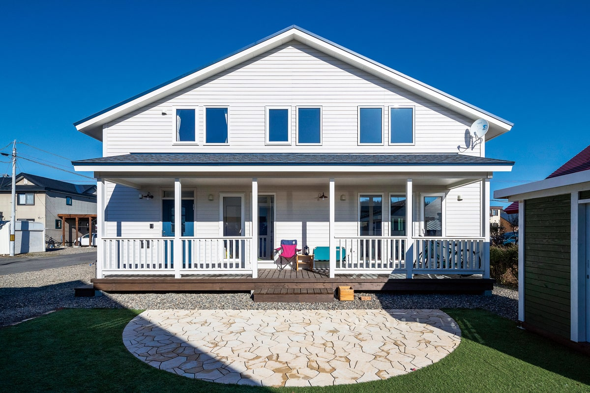 白を基調にしたカリフォルニア風の外観にマッチする外構と庭の施工も岡本建設に依頼。外物置はご夫妻で塗装した