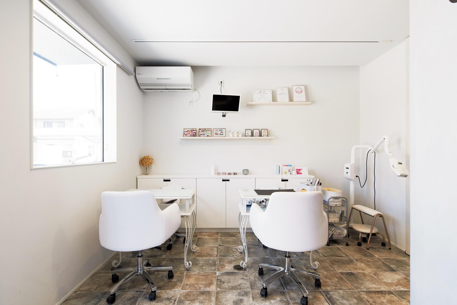 ネイルサロンのテーマカラーは白とグレー。ニュアンスあるグレータイルの床が、白を基調にしたインテリアを引き立てる。窓にはネイルの材料に影響が出る紫外線などもカットするLow-Eガラスを採用。直射日光を抑えつつ明るい空間に