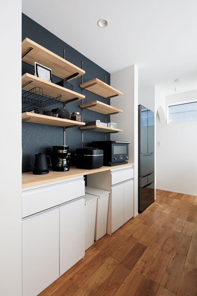 見せる収納を意識したキッチンのオープン棚。食品ストックなどは冷蔵庫の奥に設けた大容量のパントリーに収める