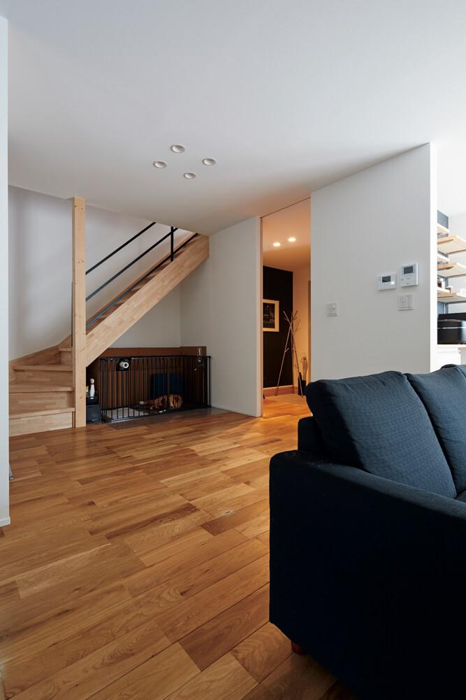 2階への階段スペースの奥には、ネイルサロンと行き来できる玄関ホール。住まいと店舗を緩やかに繋ぐ部分