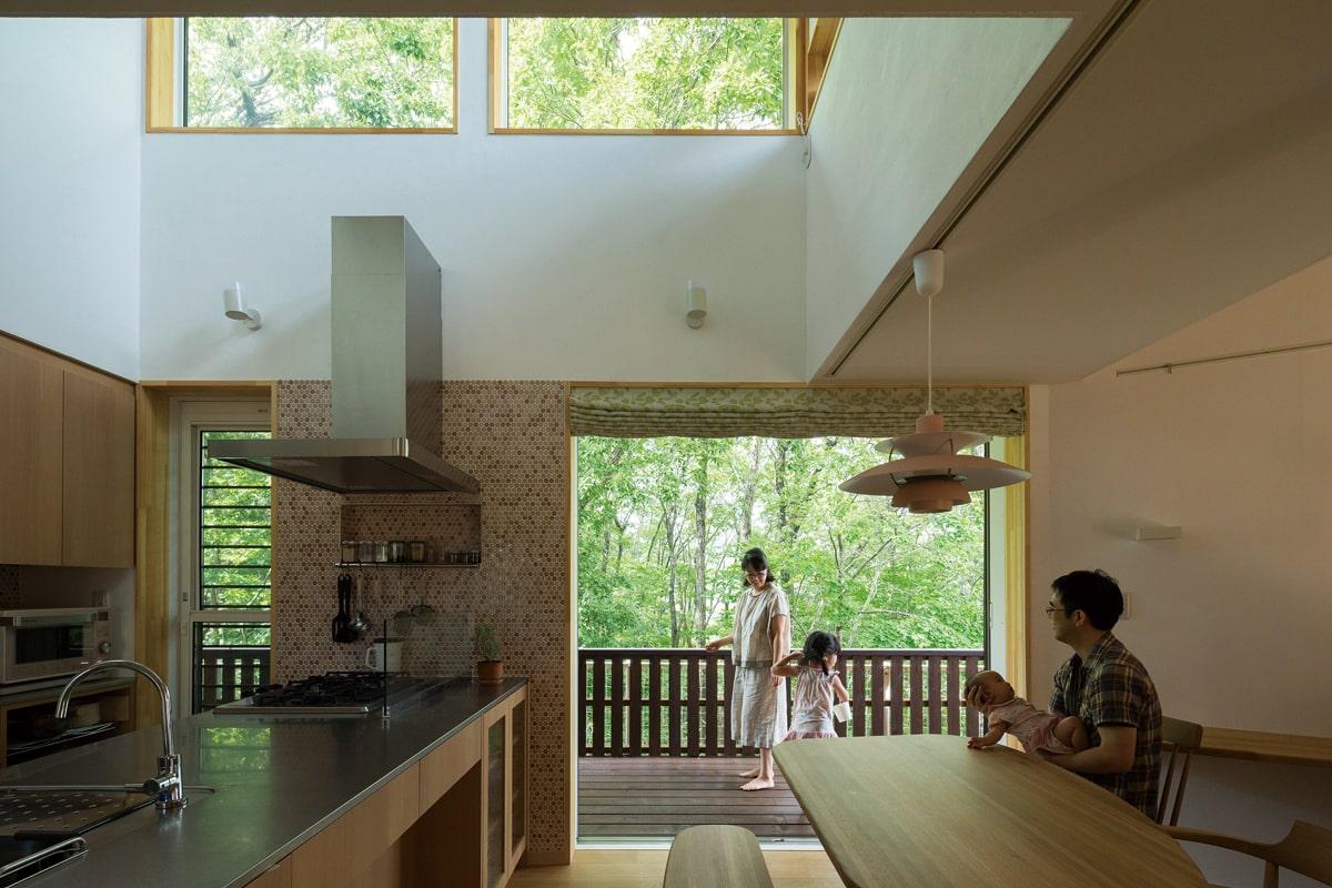 大きな開口を設け、雑木林の緑を借景に取り込んだ。緑と一体化したかのような清々しい空間