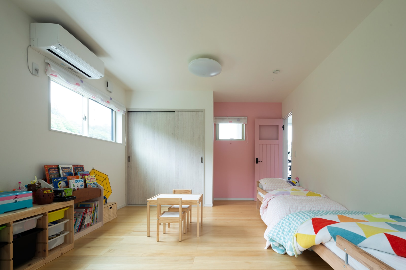 空間はシンプルにしながら、壁の一部とドアをピンク色に塗ってかわいくアクセントをつけた女の子らしい空間