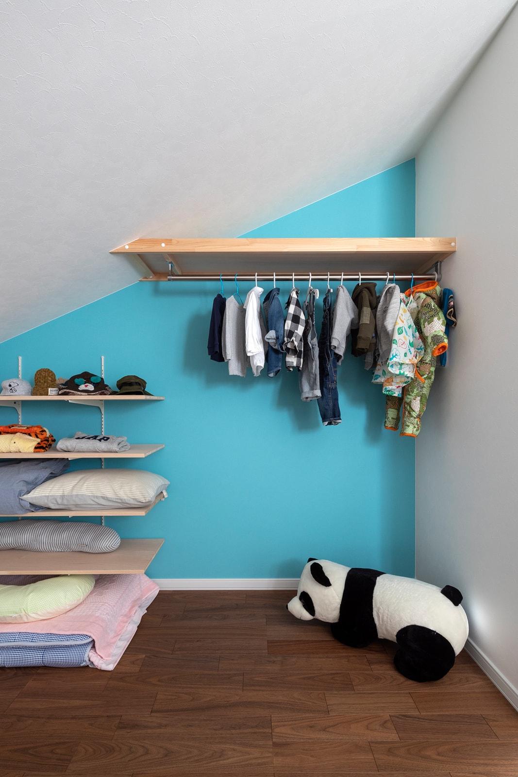 色鮮やかなアクセントウォールに、壁付けの収納棚やクローゼットハンガーを造作し、使い勝手もよく