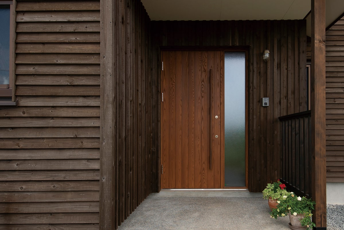外壁に合わせて玄関も木製ドアを採用。外まわりには全面的に木質感を出している