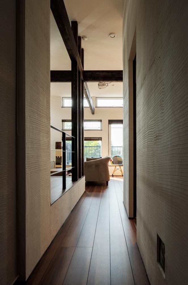 主寝室と子ども部屋の廊下から見たリビングの様子。天井が高く、外まで繋がるような開放感