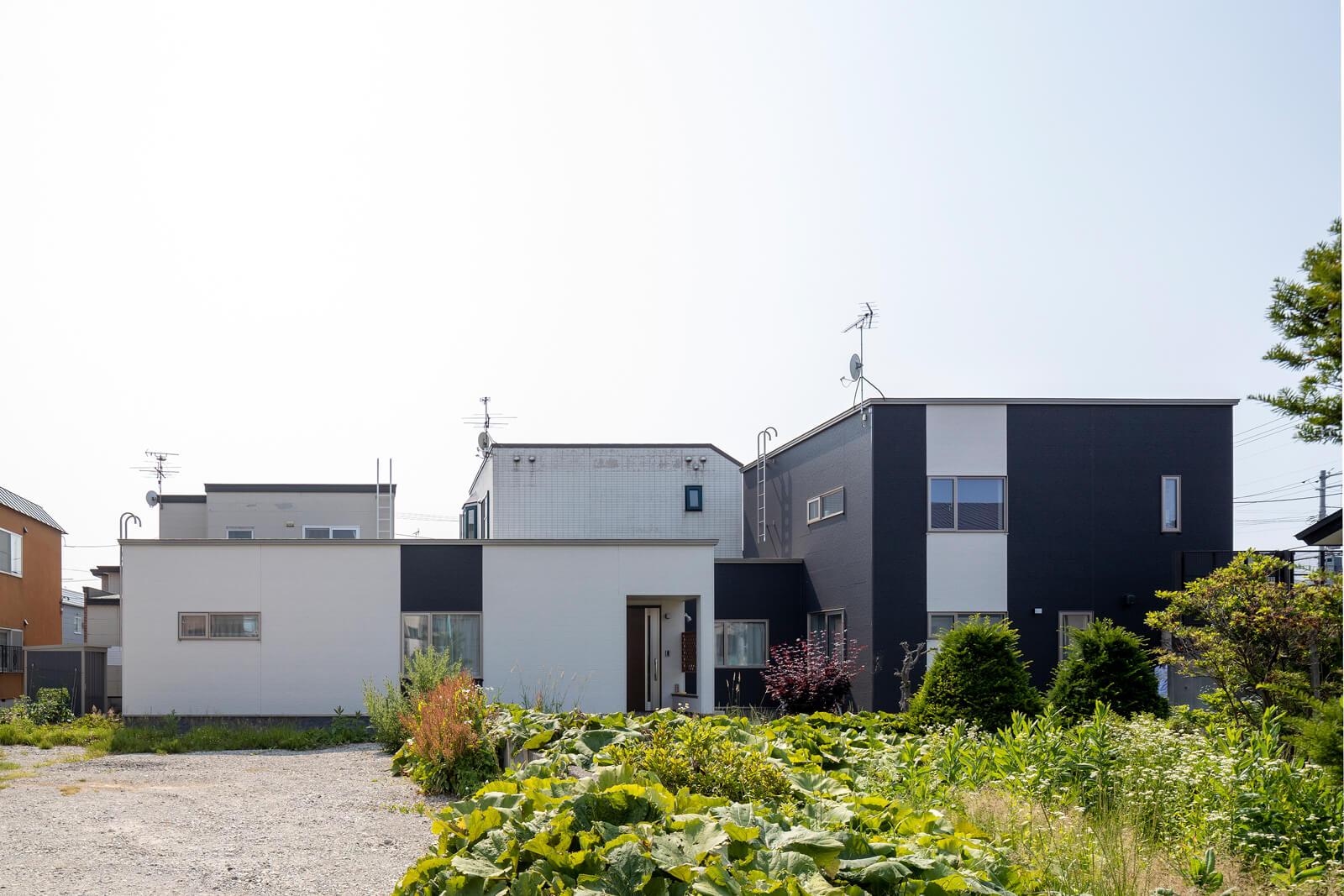 細長い敷地の形状を生かし、奥側(写真左)には平屋の親世帯の住まいを、道路側(写真右)には2階建てのFさんご家族の住まいを配置している