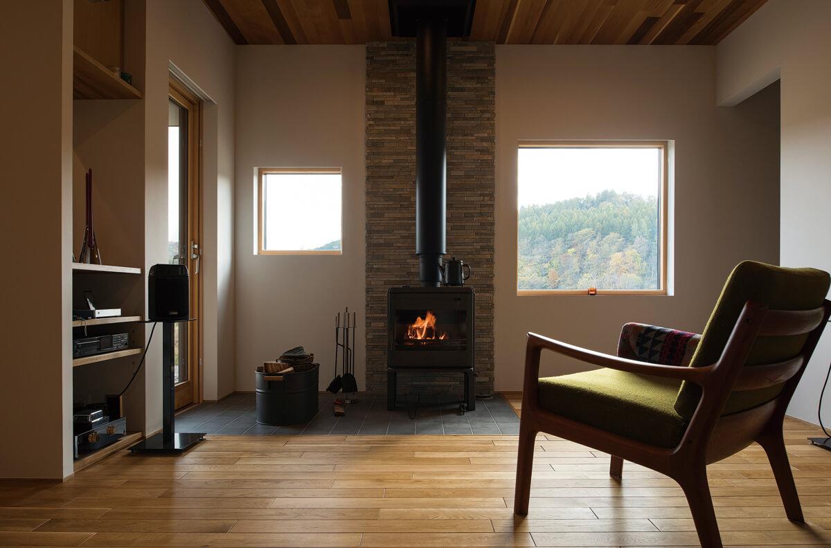 薪ストーブの炎と窓の景色が同時に楽しめる絶好のロケーション