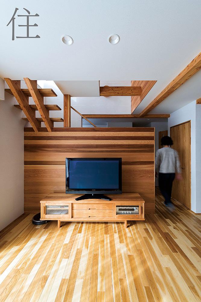 コンパクトなリビングと玄関を区切る壁は、高さを抑えることで開放感を演出。右側の通路から書斎へつながる