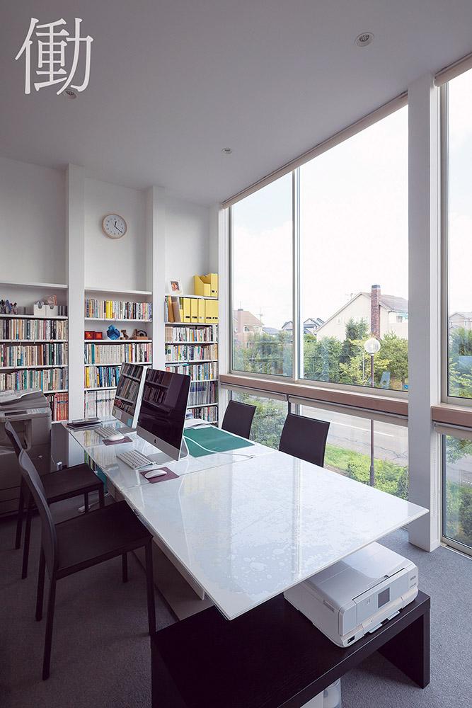 テーブルや書棚、オフィス機器を備えた2階のワークスペース