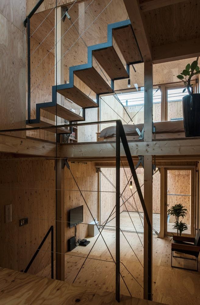2階ホールから階段越しに建物の西方向を見る。建物の強度を担保しつつ、空間の抜け感を意識した階段の構造と、吹き抜けが開放感をより高めている