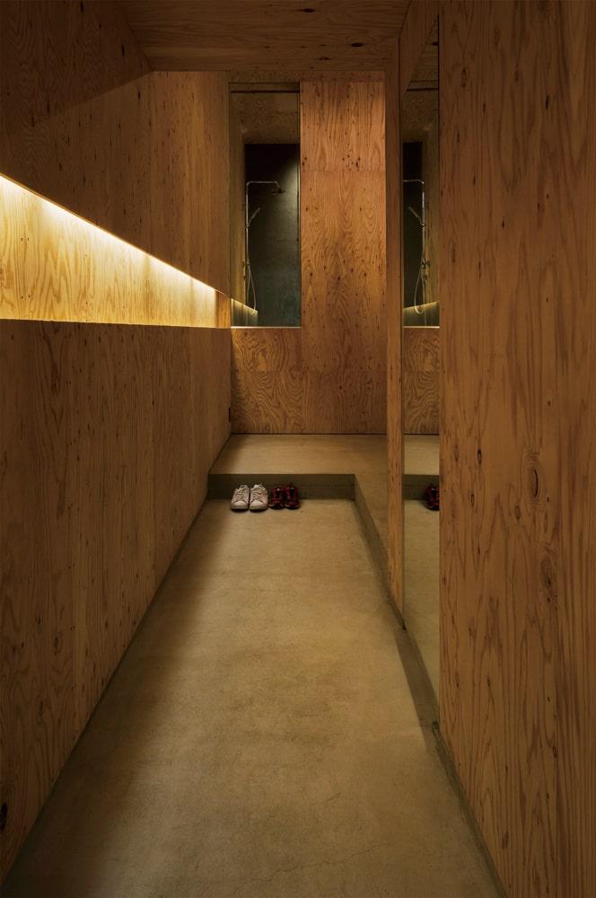 玄関扉を入って右手を見る。長手のコンクリート土間を通り室内へ。正面のFIXガラス越しに見えるのは浴室