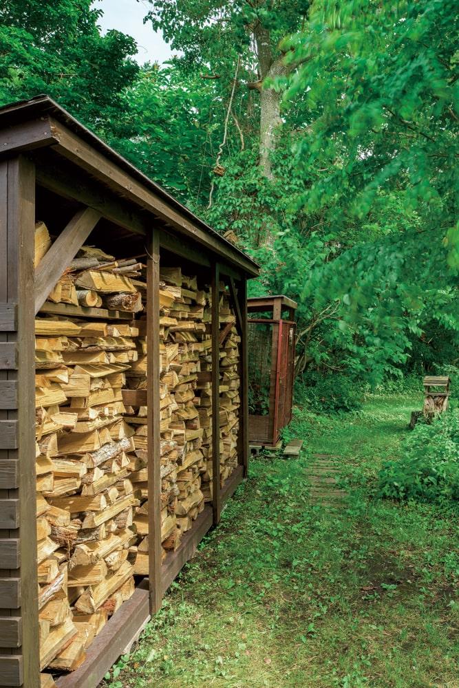 裏庭の薪小屋には、家族で準備した薪が整然と並ぶ。緑の小道の奥には、幼い息子さんたちの遊び場になっていた小川が流れている