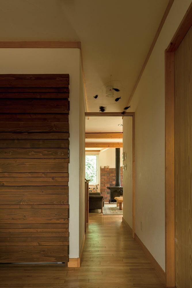 家族の暮らしに磨かれて、木肌が味わい豊かな表情を蓄えた室内。写真左側の木製の扉奥には、電気温水器が収納されている