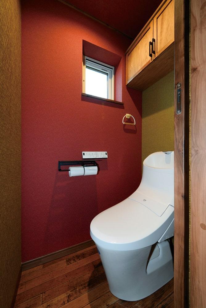 遊び心を持たせたトイレのデザイン。べんがら色のアクセントクロスが和モダンな印象を与える
