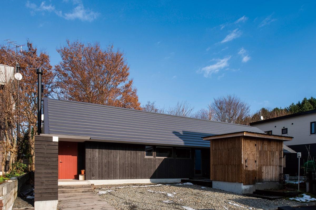 紅葉を背に建つ三角屋根の平屋の住まい。「納屋のような素朴な雰囲気にしたかった」とWさん