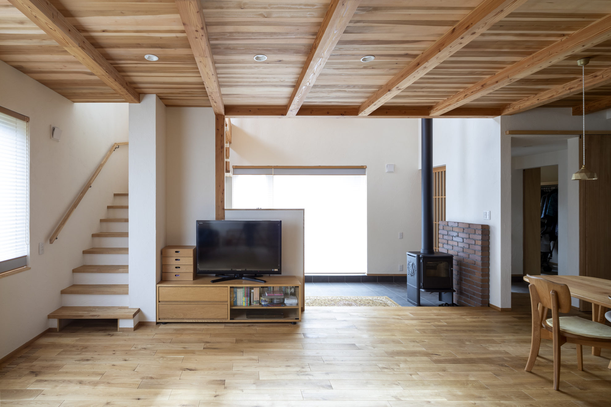 リビング、薪ストーブの置かれた土間、テラスのつながりが、空間に広がりをあたえてくれる