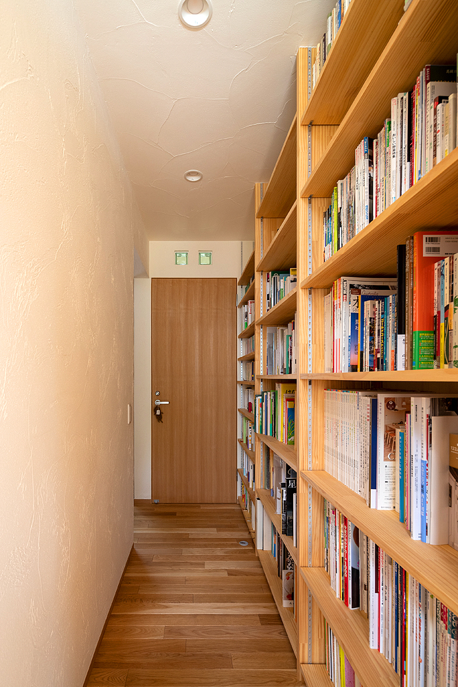 天井まで高さのある大容量の本棚は、奥さんの希望。「仕事柄、本には想い入れがあるので、大量の本が収納できる本棚はとても助かっています」