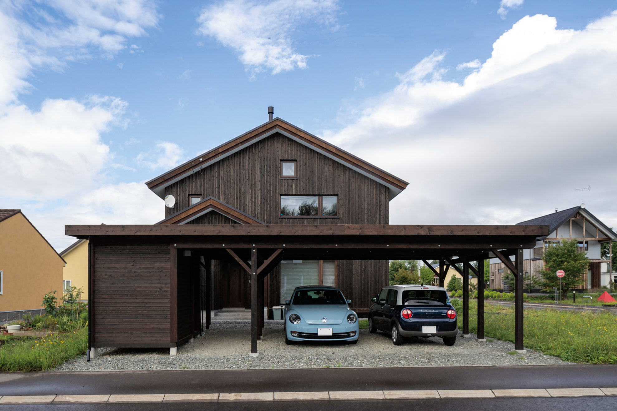 豊かな緑に囲まれたSさん宅。スギ板張りの外観は、「木の家で暮らしたい」と願ったSさんご夫妻の理想そのもの。 カーポートは車を2台とめられるようにした