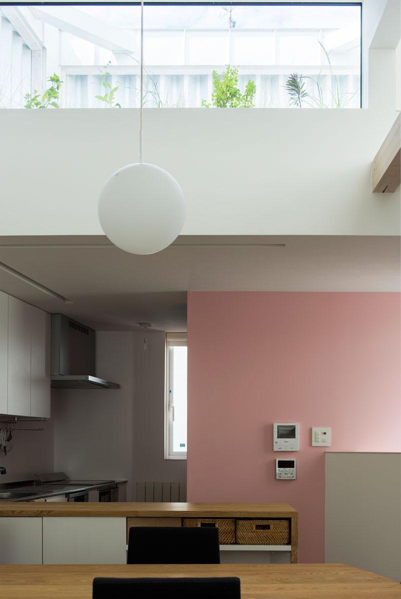 キッチンに淡い桃色のアクセントウォールを採用。