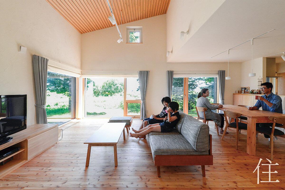 天井、壁、床に自然素材を使い、外の風景ともしっくり馴染んでいる広いリビング・ダイニング