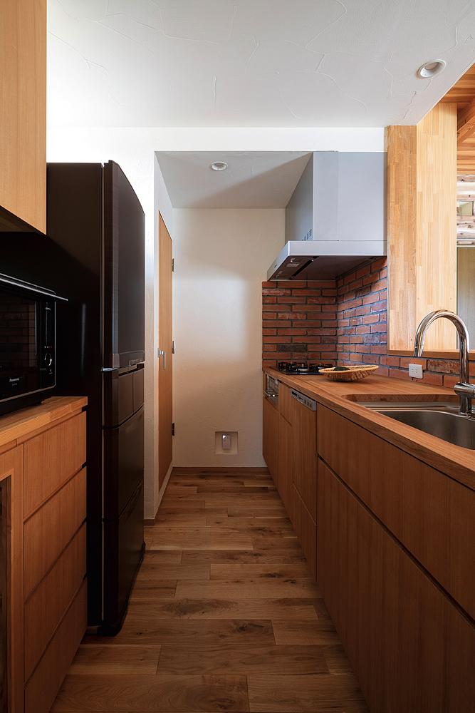 木天板のオリジナルキッチンの壁には、スライスレンガが張られている
