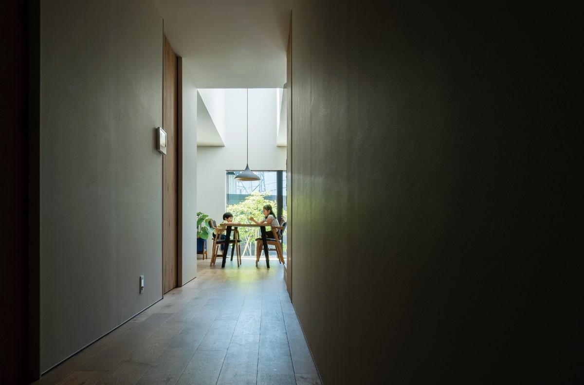 玄関から中庭へと、小道のようにつながる空間。光と影のコントラストが、家族の暮らしの場の特別感を際立たせる
