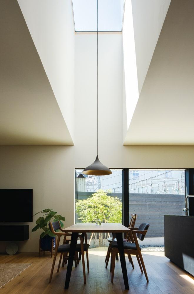 ダイニングテーブルの真上に設計された、細く高い吹き抜け。 天窓から陽の光が射し込む様は、さながら教会のような佇まい