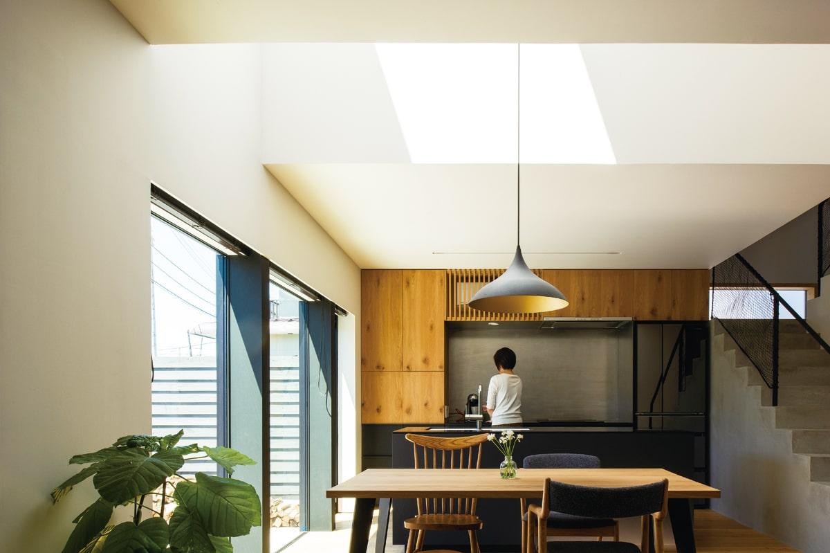 中庭と天窓の2方向から自然光が照らす、明るいダイニング・キッチン。無垢材やステンレスなどの異なる素材がバランスよく配されて、心地よい空間を形づくっている