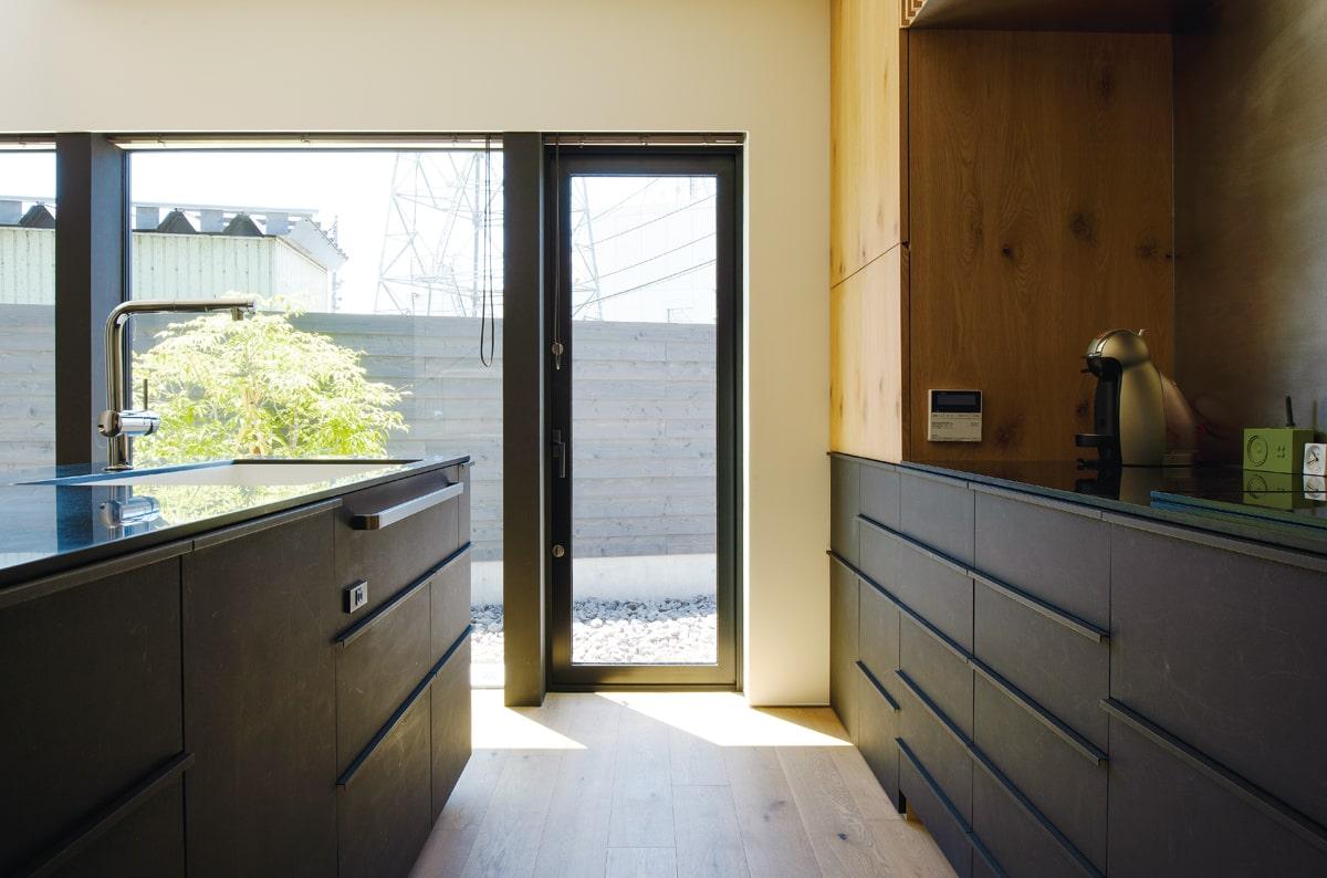 Ⅱ列型のアイランドキッチンは、奥さんの要望で黒色に。庭への動線に配慮して出入り用のドアを設けた