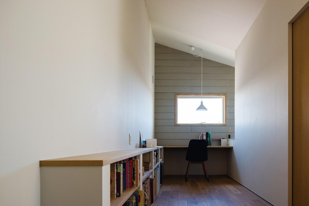 2階ホールの一部は、ご主人の書斎スペース。背の低い書棚を壁に沿って造り付けた