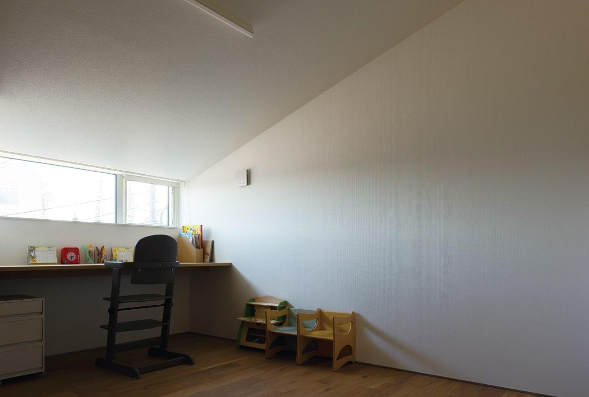 勾配天井の子ども室。造り付けのカウンターが勉強机に。横長の窓で、外の景色を切り取っている