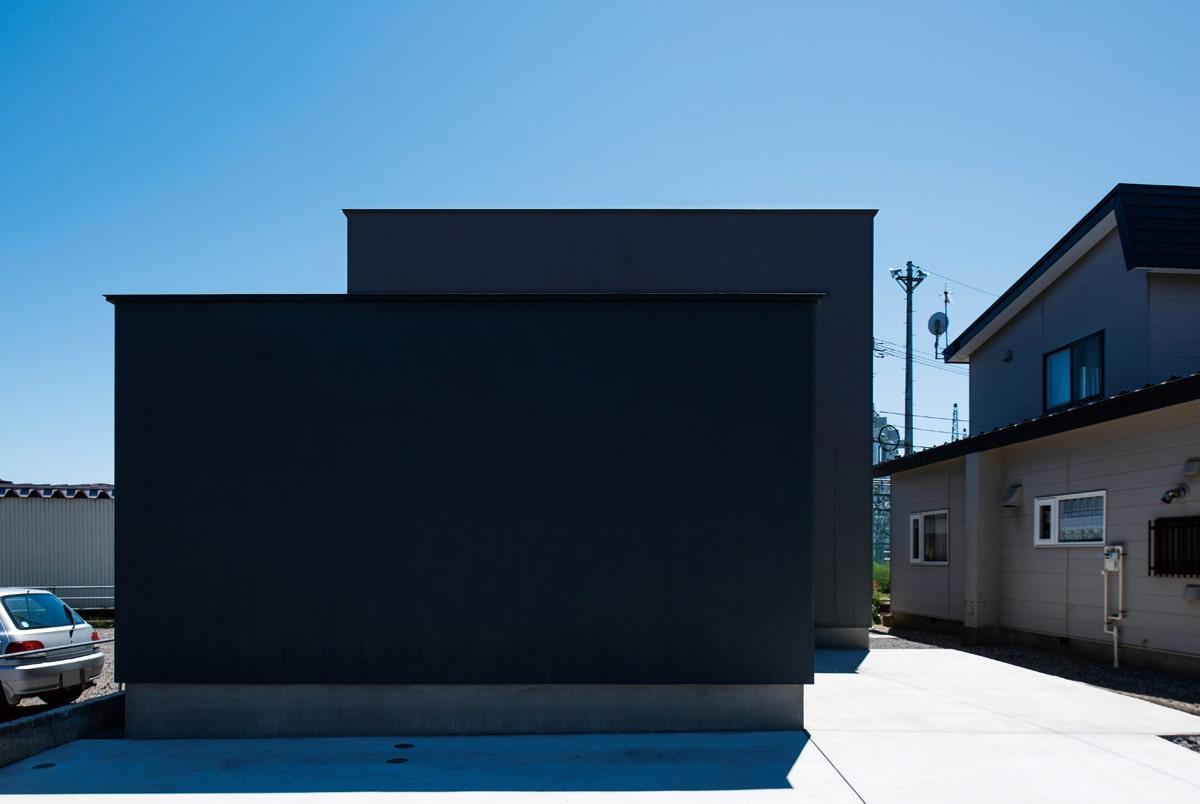真っ黒な壁が2枚連なっているように見える外観。道路側に窓がないのは、「外を気にして一日中カーテンを閉め切ることになるなら、必要なさそう」というHさんご夫妻の考えから