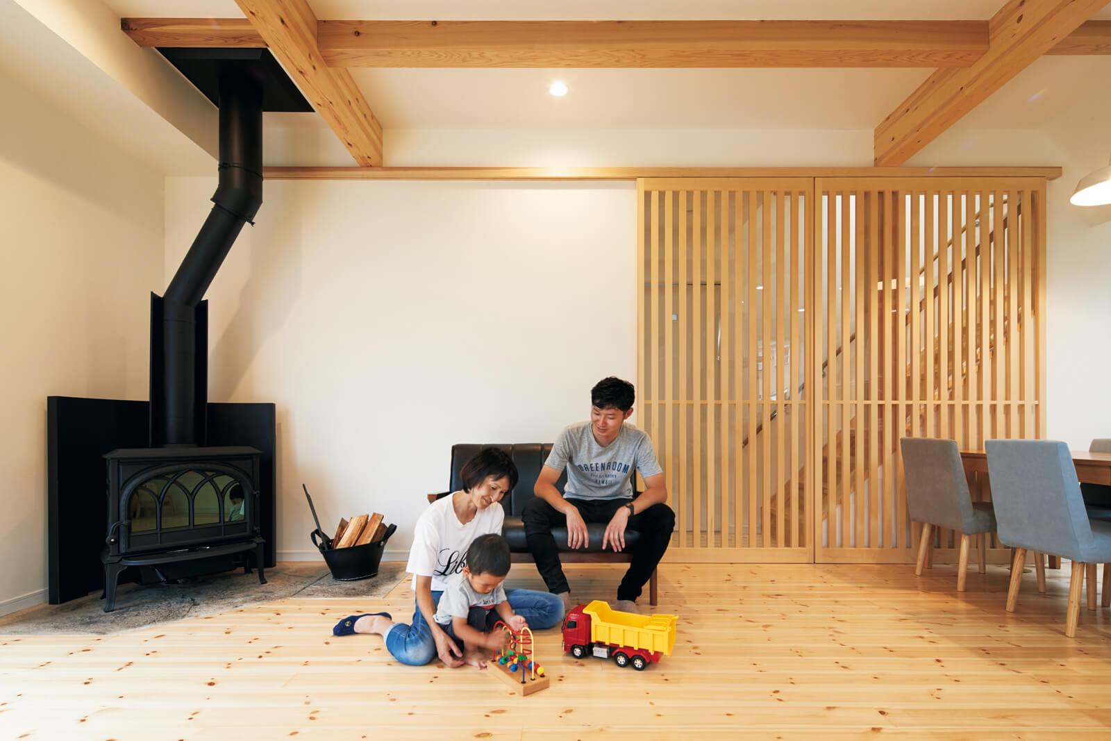 1階リビングは、天井の飾り梁と階段横の建具によってナチュラルな雰囲気と明るさが一際感じられる。木の風合いと薪ストーブが、家族の和やかな団らんを包み込む