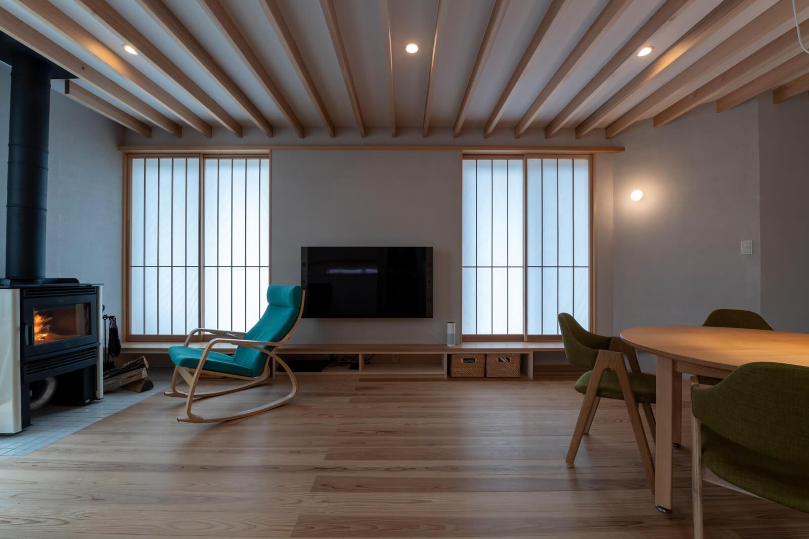 梁が連なるLDKの掃き出し窓の段差は収納としてもベンチとしても活躍。薪ストーブの炎を眺める時間は、格別のひととき。窓に設えた建具も、全体に配慮して緻密なデザインが施されている