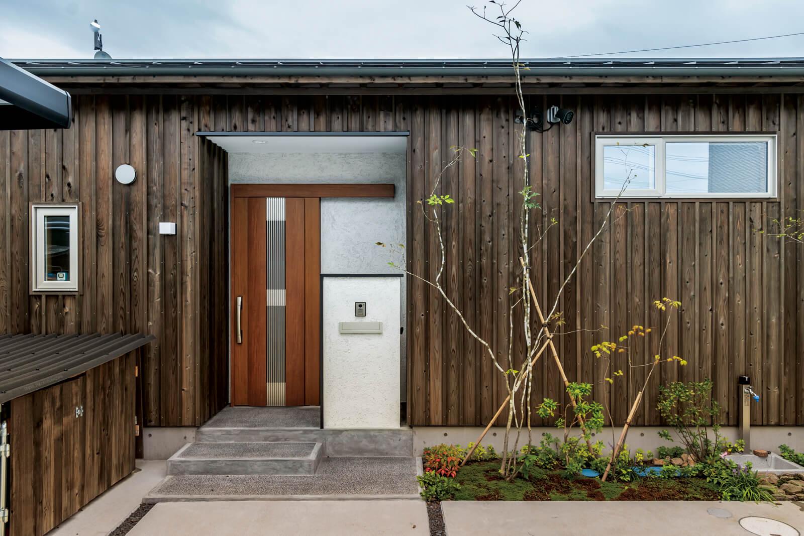 玄関扉は引き戸を採用。玄関前にはアオダモやキリシマツツジなどが植えられた