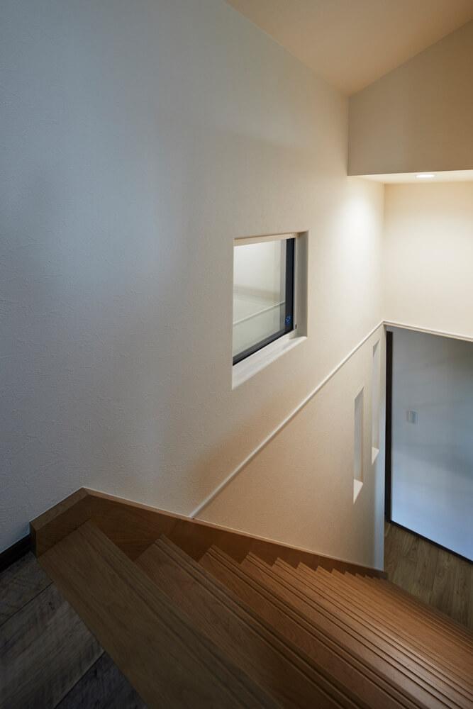 階段の壁に開口部を設けて空間にアクセントをつけている