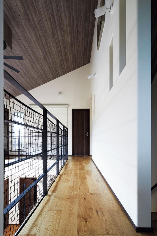 吹き抜けに面した2階廊下にはアイアンの手すりを造作。ナチュラルな空間の引き締め役になっている