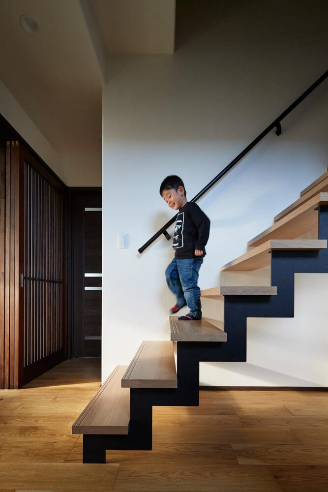 リビング空間におしゃれなアイアン階段が映える。光を通す階段下はフリースペースになっている