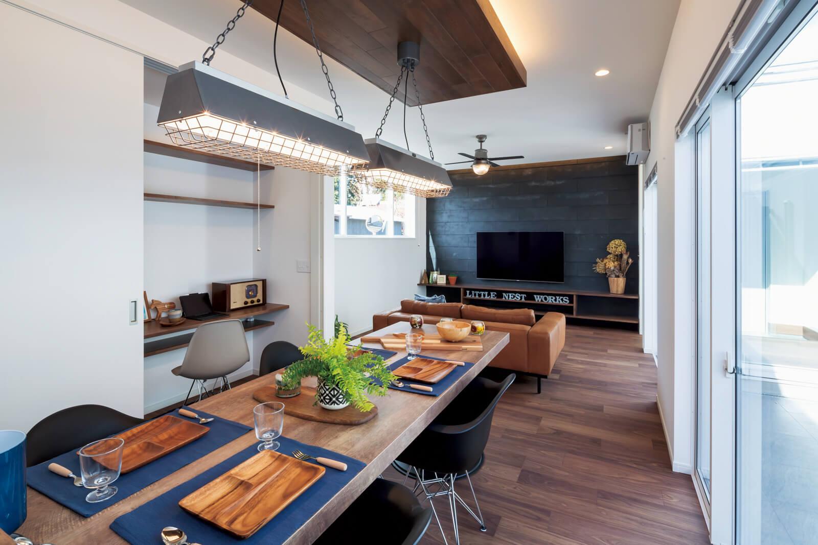 中庭に面した窓から陽射しが射し込むLDK。木製のテレビボード背 後の壁面は、システムキッチンまわりのタイルと同素材を使用。アクセ ントにダークグレーをバランスよく配置