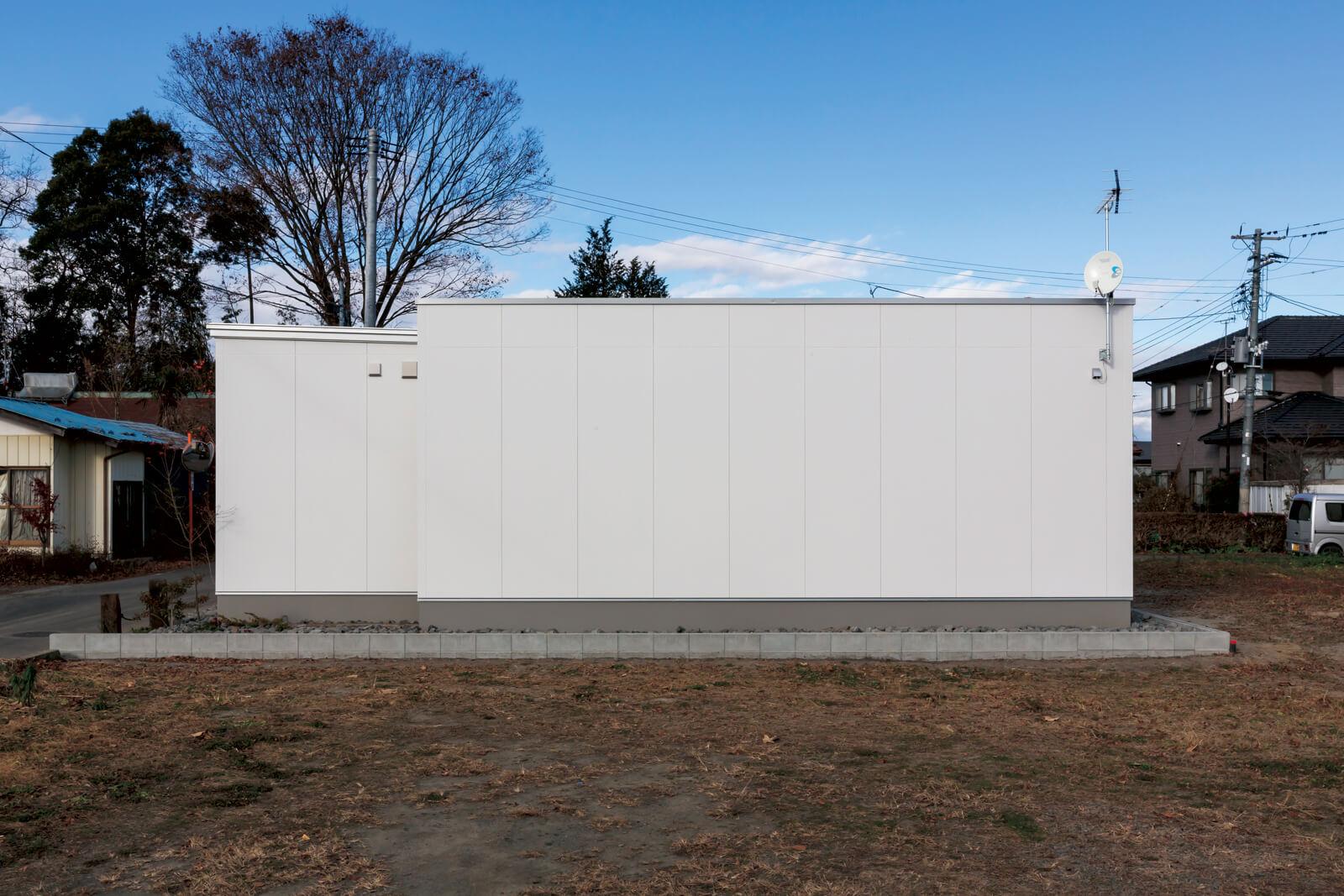 外壁は防火サイディングに白の塗装を施し、シンプルモダンに。夏は植栽が白い壁のアクセントとなる