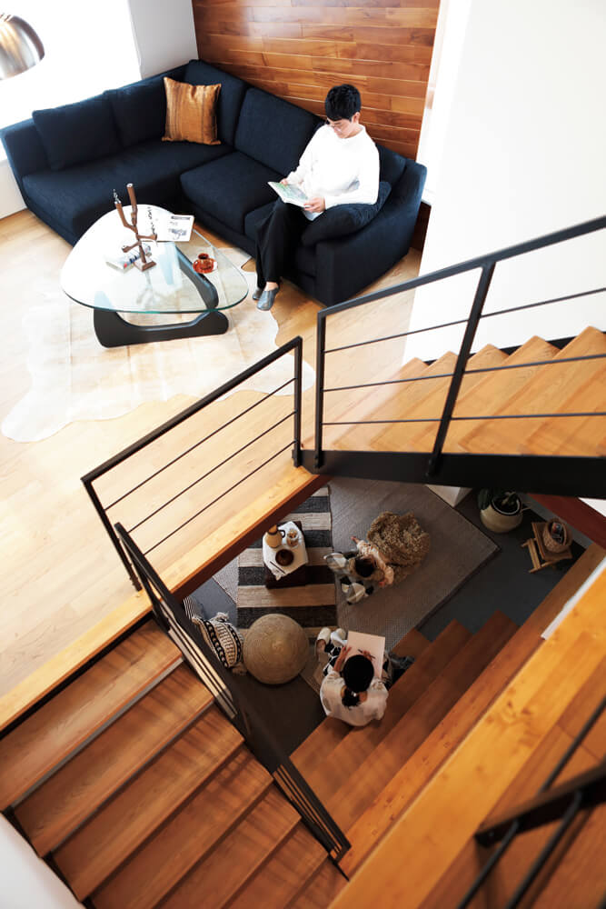 2階から1.5階のリビングと半地下を一望する。家のどこにいても家族の気配が柔らかく伝わる