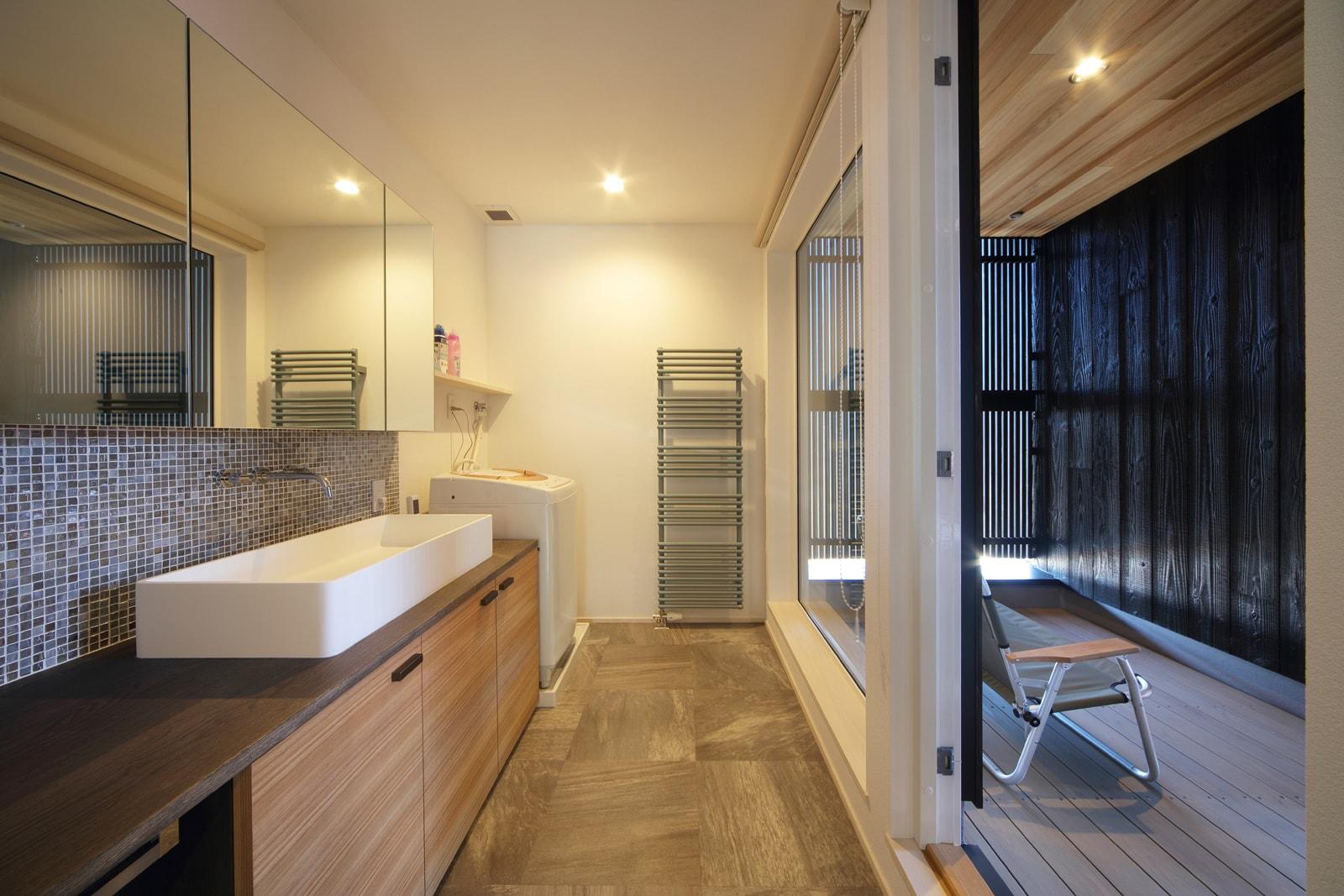 ユーティリティの窓際に、モスグリーンの温水パネルヒーターで柔らかいアクセントを。タオルをかけられるハシゴ型デザインのもので機能性も確保した