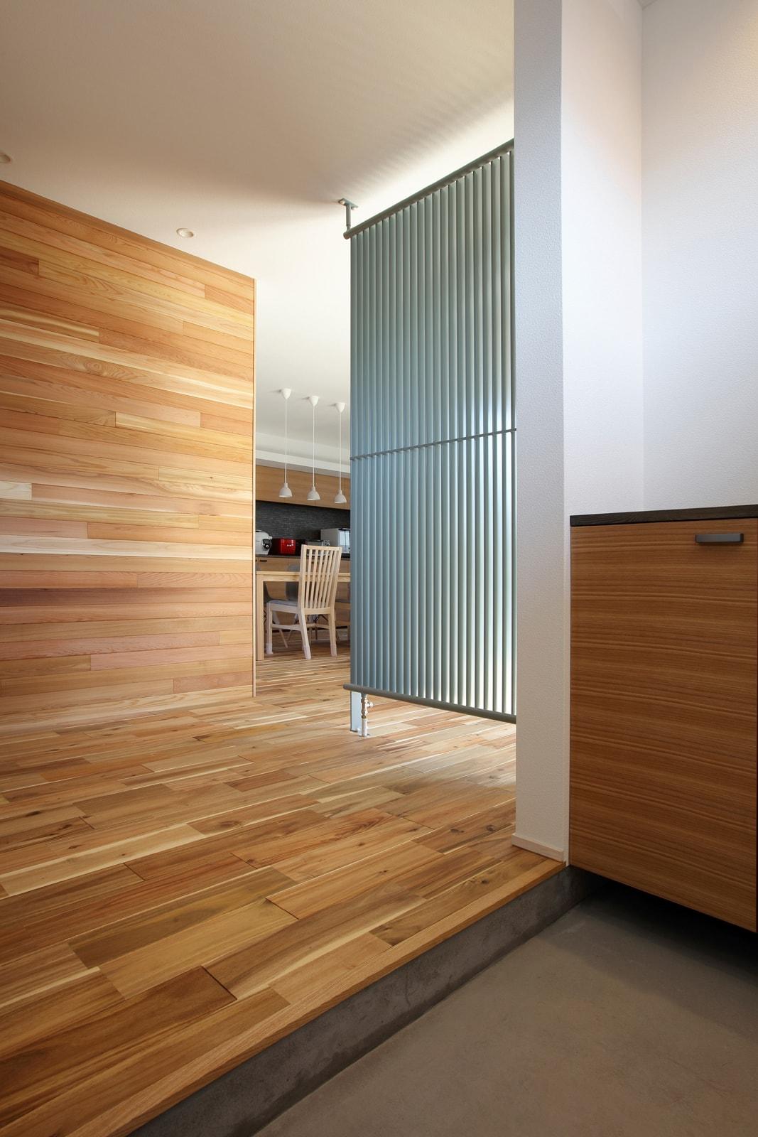 玄関ホールとリビングを仕切る大型のパネルヒーター。ドアの開け締めなど外気が入ってくる玄関でも、パネルヒーターの暖房効果で暖か