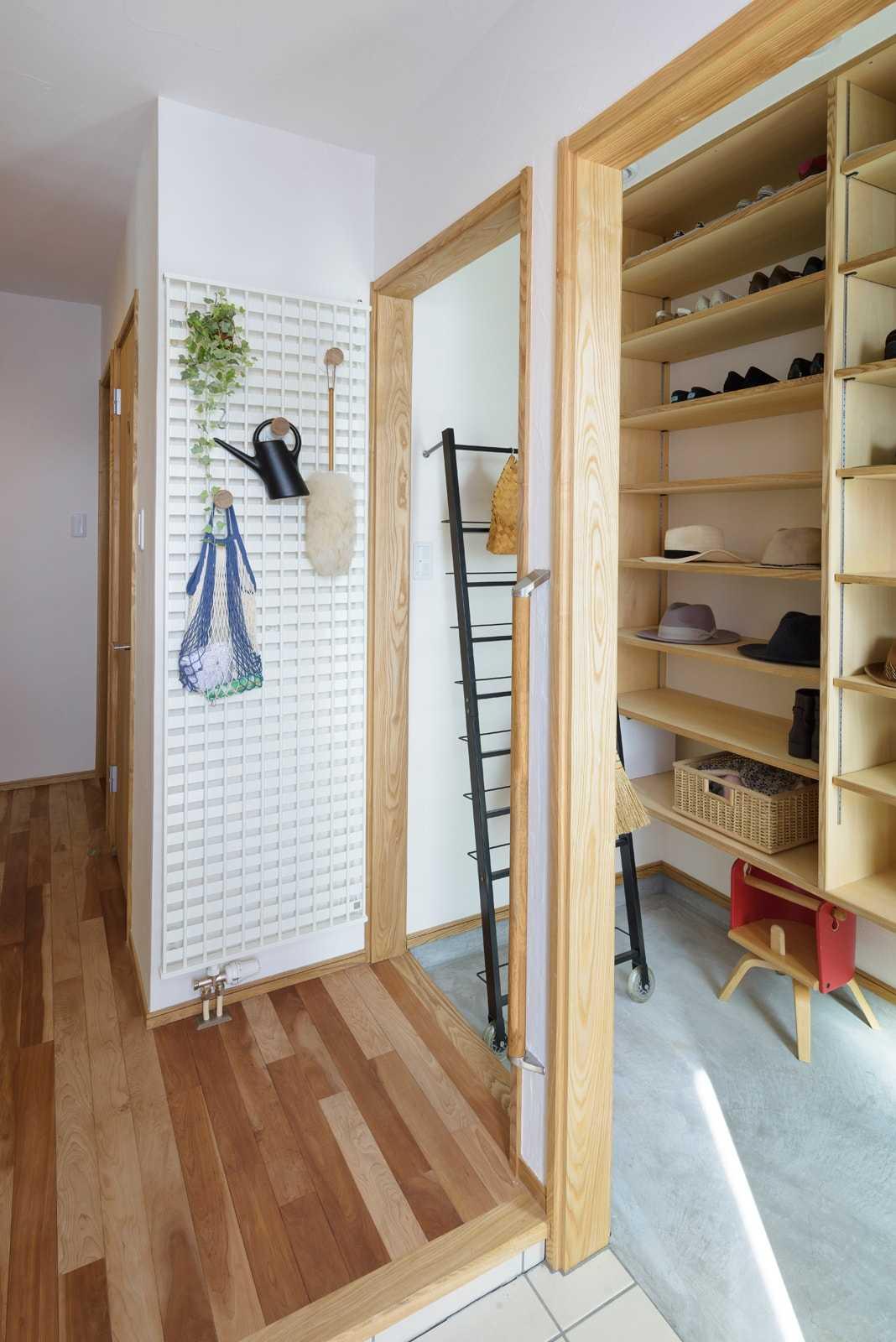 玄関ホールのコート掛けを兼ねたパネルヒーターは、見せる収納にして空間に豊かさをプラス