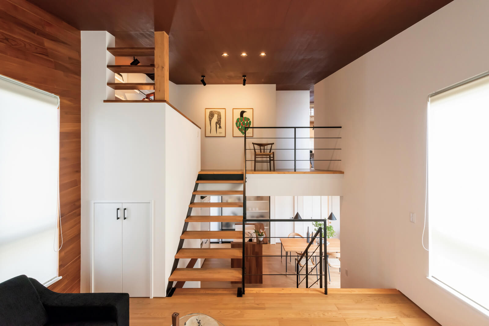 1.5階のリビングから1階のダイニング・キッチンと2階アートスペースを見る。スキップフロアの家には、階段を上がるたびに違った空間が広がる楽しさがある