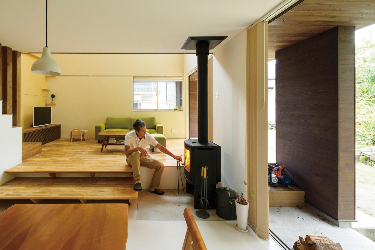 スキップフロアを採用した土間仕上げのダイニング・キッチンとリビング空間。自然体で薪ストーブの前に腰をおろせる