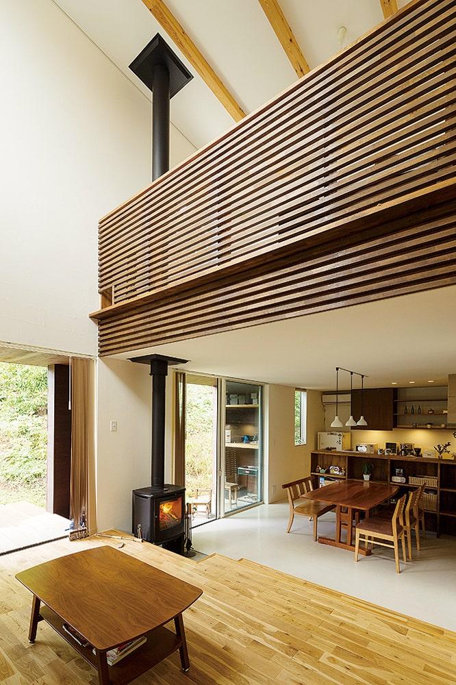吹き抜けのリビング。木質感たっぷりな壁デザインにはキャットウォークを設けている
